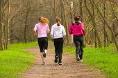 Three girls running through the park