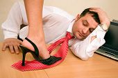 Woman's leg stepping on businessman red tie
