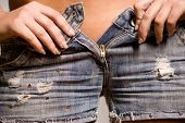 Young girl unzipping her jeans