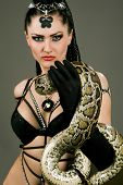 stock photo of lilith  - Gorgeous brunette holding boa constrictor - JPG