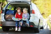 Two Adorable Little Girls Ready To Go On Vacations With Their Parents. Kids Sitting In A Car Examini poster
