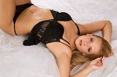 Gorgeous woman wearing erotic black lingerie over white