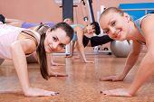 Young slim women doing push-up exercises