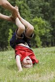 Young boy doing upside down on green grass