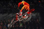 stock photo of moto-x  - A freestyle moto-x rider goes through a trick during an indoor competition.
