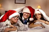 Manager with two his subordinates look out  cover in bed on New Year's night
