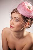 Portrait of pretty young woman in pink bonnet with voile. Vintage Make-up