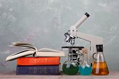 Chemical Flasks, Books And Microscope On The Desk On Green Background poster