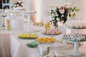 Delicious Eclairs,macaroons,cupcakes, Desserts And Sweets On Table Party At Wedding Reception. White poster