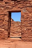 Old mud wall and entrance build with red rocks in Wupatki pueblo
