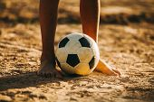 Close Up Picture Of An Old Ball And Foot Of A Poor Kid Who Is Playing Football In The Sunshine Day. poster
