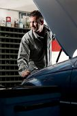 image of car repair shop  - Smiling mechanic controlling car engine - JPG