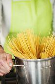 Woman Preparing Spaghetti In Pot, close-up
