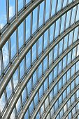 image of purlin  - Silver metal curved roof joists in a conservatory with glass panes in between and a blue sky and clouds beyond - JPG