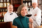 Restaurant manager happy taste glass of red wine in bar