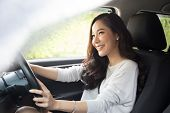 Asian Women Driving A Car And Smile Happily With Glad Positive Expression During The Drive To Travel poster