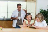 Kinder mit Tablet in der Küche zusammen mit Vater dahinter