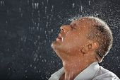 Tanned man wearing white wet shirt stands in rain and drops fall on his head.
