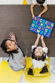 Flat Lay Shot Of Asian Teachers Play Colorful Alphabet Puzzle Toy With Asian Students Together, They poster