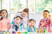 Science Teacher And Asian Students In Laboratory Room, They Blowing Bubbles, Colorful Test Tube And  poster