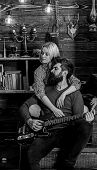 Lady And Man With Beard On Dreamy Faces Hugs And Plays Guitar. Romantic Evening Concept. Couple In L poster