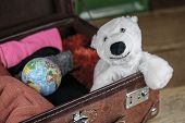 Polar Bear Toy In Suitcase Of A Traveler, Also Small Globe Among The Clothes, Packed Into Open Vinta poster
