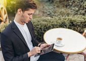 Smart Business Man Using His Tablet While Having Breakfast At Coffee Shop, Businessman Holding Cup O poster
