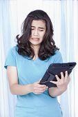 Chica adolescente mirando con asco en computadora Tablet en mano