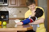stock photo of physically handicapped  - Father helping disabled son putting fruit into bowl in the kitchen - JPG
