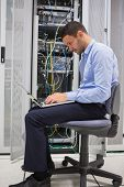 Man on his laptop beside servers in data center