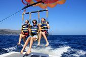 picture of parasailing  - Father and Twin Daughters Parasailing Against a Blue Summer Sky - JPG