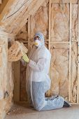 Worker filling walls with insulation in construction site