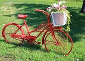 Pretty red bike with basket of flowers