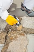 image of grout  - Worker Brush Primer Grout Of Stones Joint - JPG
