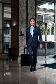 stock photo of carry-on luggage  - Business executive entering hotel lobby with his luggage - JPG