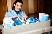 stock photo of disinfection  - Working staff arranging toiletries in a wheel cart - JPG