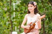 stock photo of ukulele  - Asian girl with ukulele guitar outdoor in happy concept - JPG