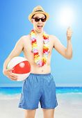 Smiling male in swimming shorts, holding a beach ball and giving thumb up, on a beach next to a sea