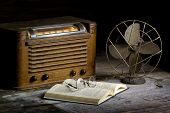 stock photo of primite  - vintage radio and fan on primitive desk - JPG