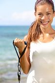 Fitness girl training at beach with elastics resistance bands. Fit sporty woman strength training bi