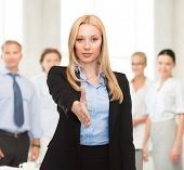 woman with an open hand ready for handshake in office