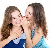 woman's secret, two young beautiful women friends whisper funny news