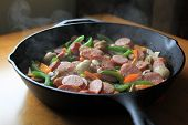 Cast iron pan with Kielbasa,onions and peppers on table