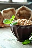 stock photo of bengal-gram  - raw chickpeas in a brown bowl with herbs - JPG