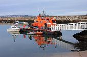 stock photo of outboard engine  - lifeboat reflected in the waters of Brixham harbour - JPG