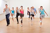 stock photo of physical exercise  - Large diverse group of people doing aerobics exercises in a class in a gym in a health and fitness concept - JPG