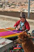 Peruvian woman weaving and her llama with city of cusco in background, Cusco, Peru, July 9, 2009