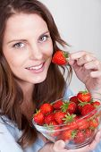 Woman Enjoying A Bowl Of Strawberries