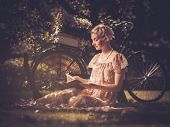 Blond retro woman with a book in summer dress sitting on a meadow