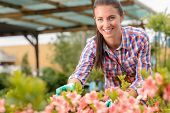 Smiling florist working in garden center looking at camera